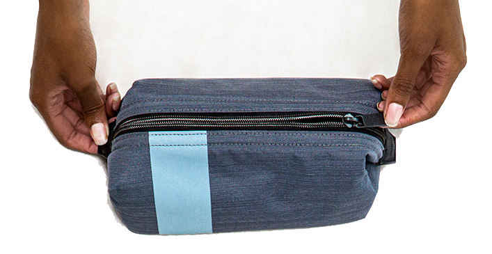 Lifestyle image of gray and blue travel set including cosmetic bags, a tote bag and glasses holder