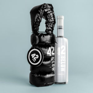 Image of 42Below Vodka next to it's puffy parka style fabric carrier bag with top handle