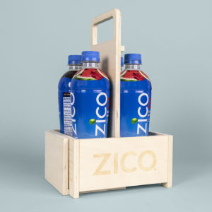 Image of Zico coconut water bottles in a convertible multi-use branded wooden carrier case